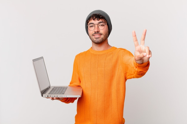 Homem nerd com computador sorrindo e parecendo amigável, mostrando o número dois ou o segundo com a mão para a frente, em contagem regressiva