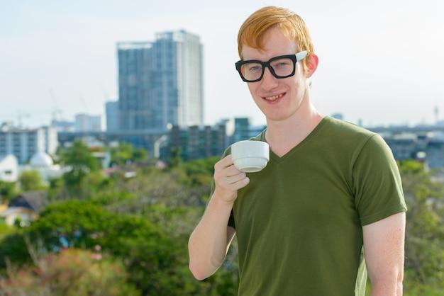 Homem nerd feliz com cabelo vermelho bebendo café com vista da cidade