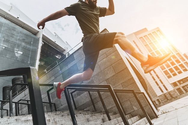 Homem no ar. vista de baixo ângulo de jovem em roupas esportivas pulando