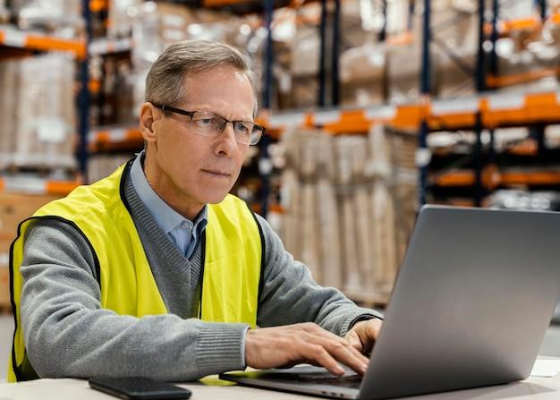 Homem no armazém trabalhando no laptop