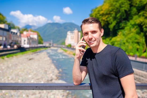Homem no aterro de um rio de montanha em uma cidade europeia,