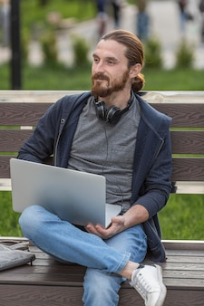 Homem no banco ao ar livre com laptop