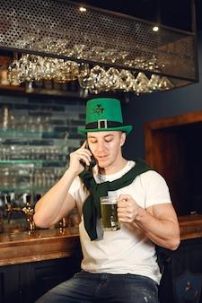 Homem no bar com cerveja. guy comemora o dia de são patrício. homem com um chapéu verde.