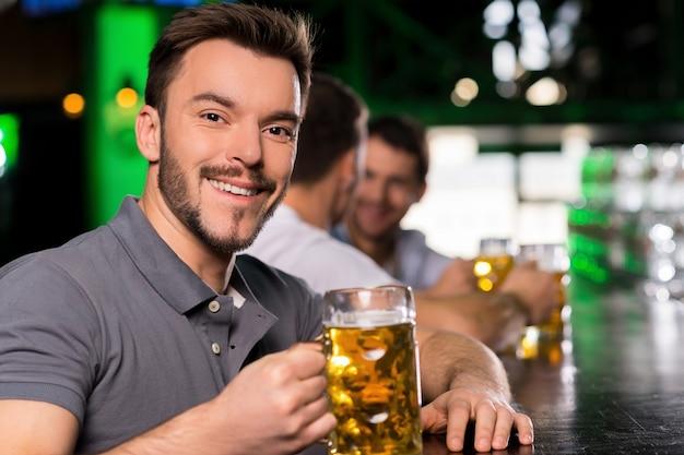 Homem no bar. jovem bonito bebendo cerveja em bar e sorrindo