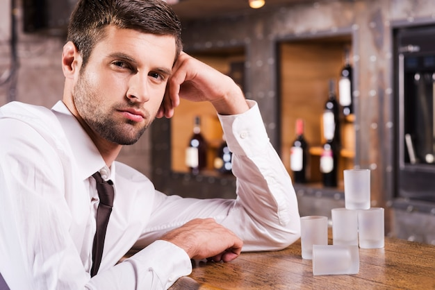 Homem no bar. jovem bonito de camisa e gravata encostado no balcão do bar e olhando para a câmera enquanto copos vazios em pé perto dele