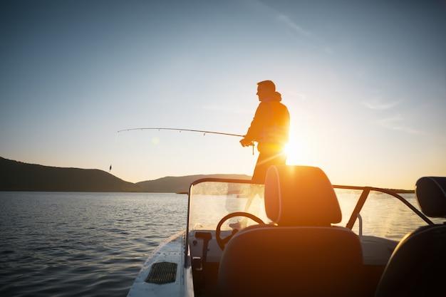 Homem no barco de pesca ao pôr do sol