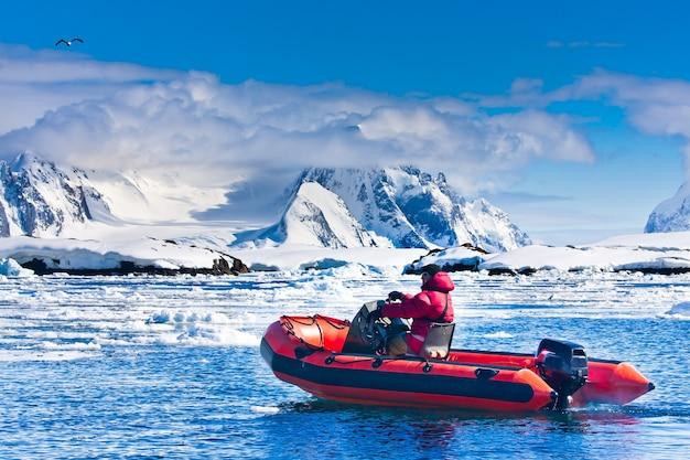 Homem no barco vermelho nas águas antárticas