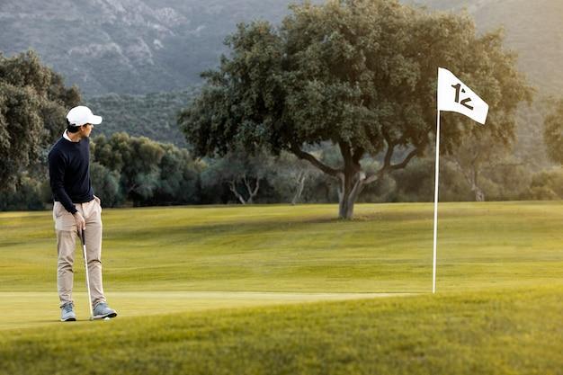 Homem no campo de golfe próximo à bandeira
