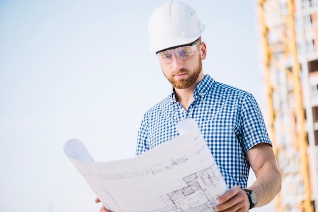 Homem no capacete de segurança que olha o papel de modelo