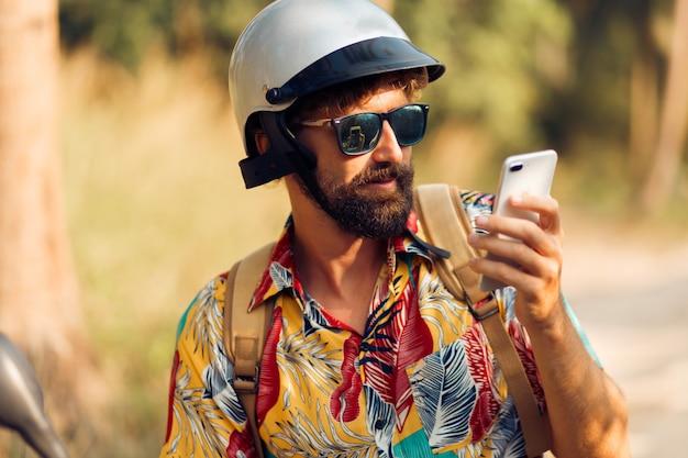 Homem no capacete sentado na moto e usando telefone celular