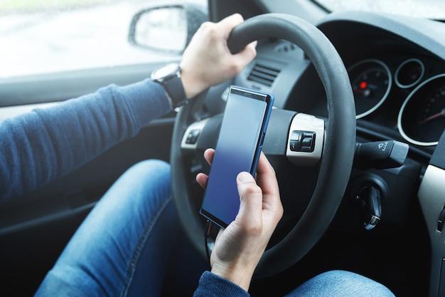 Homem no carro está usando smartphone. conceitos de compartilhamento de viagens, segurança na direção ou navegação gps.