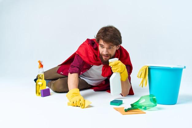 Homem no chão limpando o material de limpeza da casa profissional.