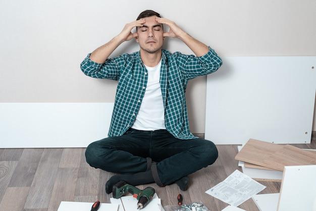 Homem no chão segurando a cabeça, dificuldade de montar móveis.