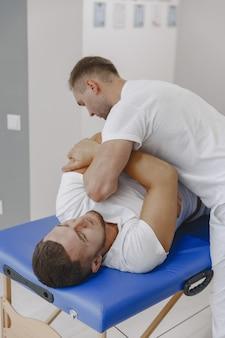 Homem no consultório médico. fisioterapeuta está reabilitando as costas.