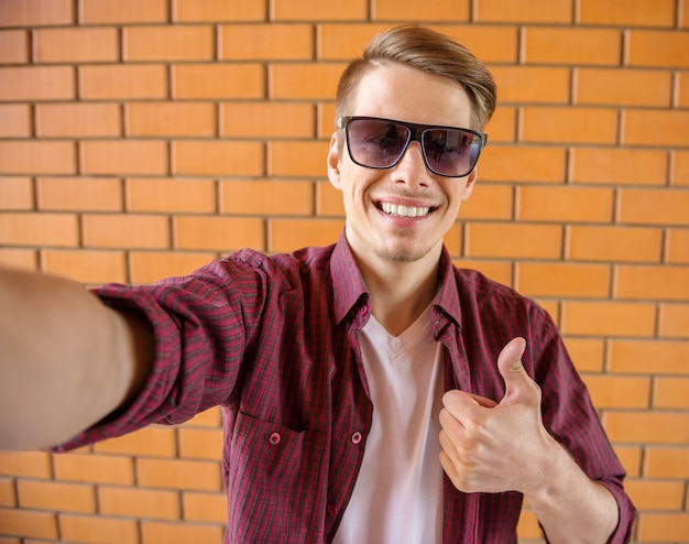 Homem no desgaste ocasional esperto que faz o selfie na parede de tijolo.