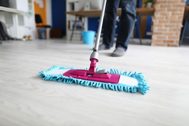 Homem no escritório esfrega o chão