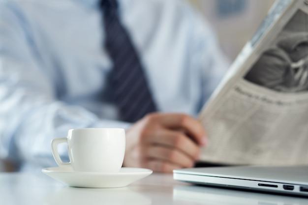 Homem no escritório lendo jornal e bebendo café