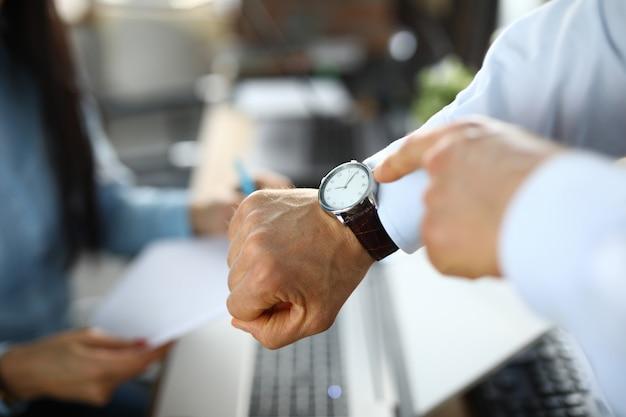 Homem no escritório mostra um dedo no relógio