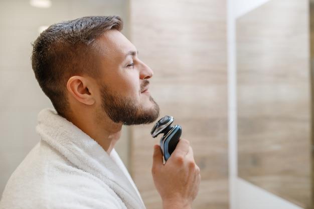 Homem no espelho raspa a barba com um barbeador elétrico no banheiro, rotina de higiene matinal.