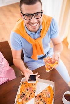 Homem no estilo casual usar computadores no escritório e comer pizza
