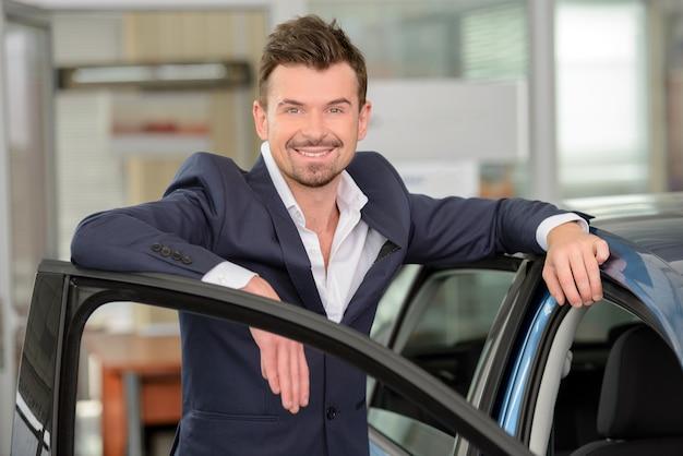 Homem no formalwear que inclina-se no carro e que olha a câmera.