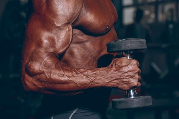 Homem no ginásio. cara musculoso fisiculturista fazendo exercícios com halteres. pessoa forte com mão masculina tensa com barra de veias. jornal tonificação moderna.