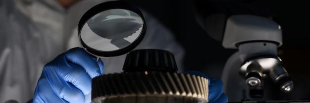 Homem no laboratório examina partes do veículo closeup