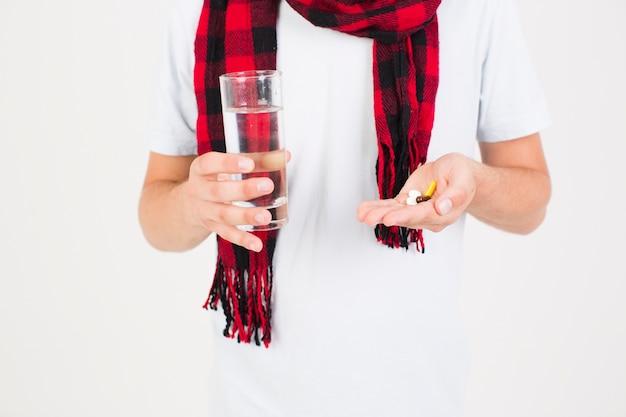Homem no lenço com comprimidos na mão