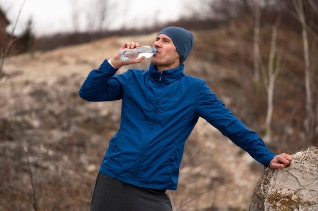 Homem no meio do tiro bebendo água na natureza
