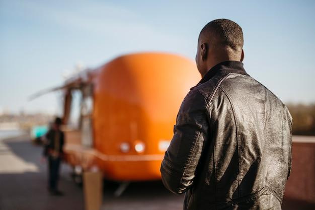 Homem no meio do tiro caminhando em direção ao food truck
