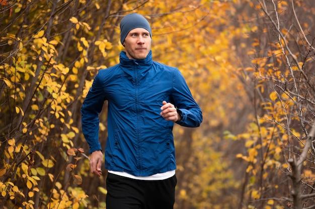 Homem no meio do tiro correndo na trilha na floresta