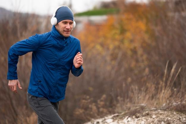 Homem no meio do tiro correndo pela natureza
