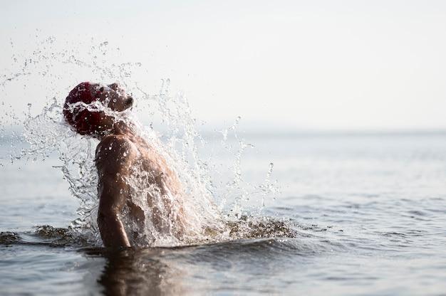 Homem no meio do tiro espirrando para fora d'água