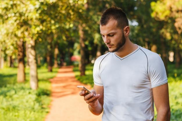 Homem no parque após treino de fitness, verificando seu smartphone