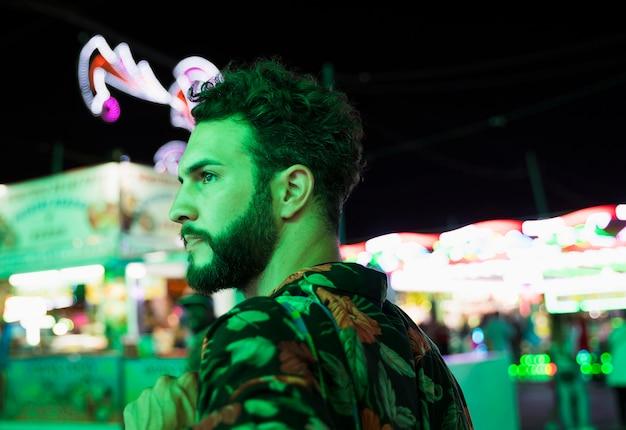 Homem no parque de diversões, olhando para longe