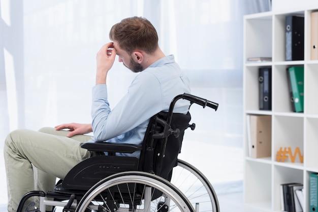 Homem no pensamento de cadeira de rodas