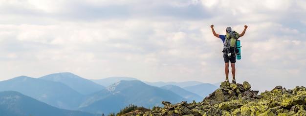 Homem no pico da montanha. cena emocional. jovem com mochila em pé com as mãos levantadas no topo de uma montanha e apreciando a vista para a montanha. alpinista no topo da montanha. esporte e vida ativa conceito.