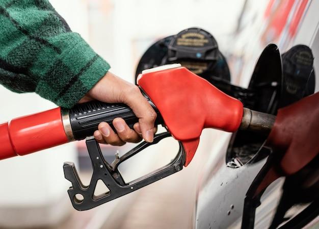 Homem no posto de gasolina com o carro de perto