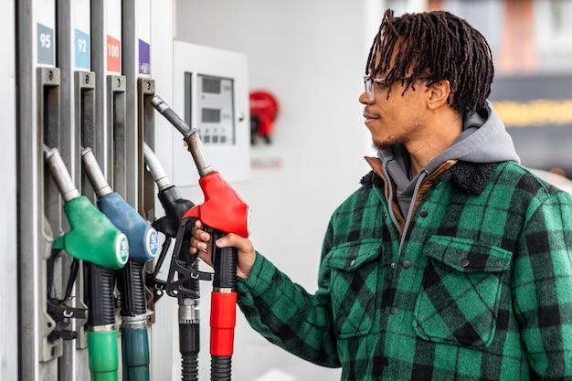 Homem no posto de gasolina com o carro