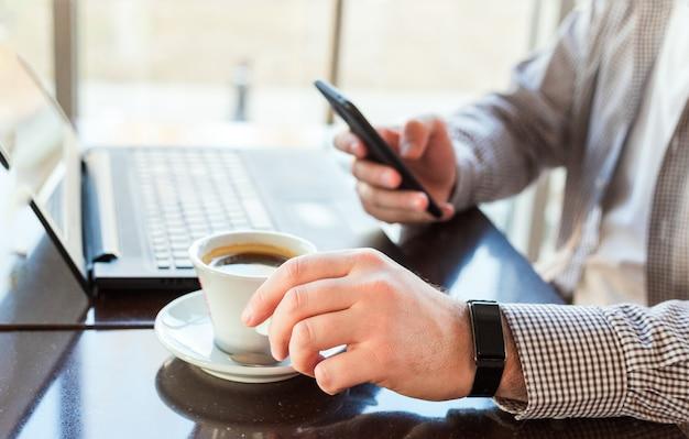 Homem no relógio inteligente, bebendo café no espaço de trabalho. homem usando laptop, segurando o telefone inteligente para trabalho ou estudo de negócios