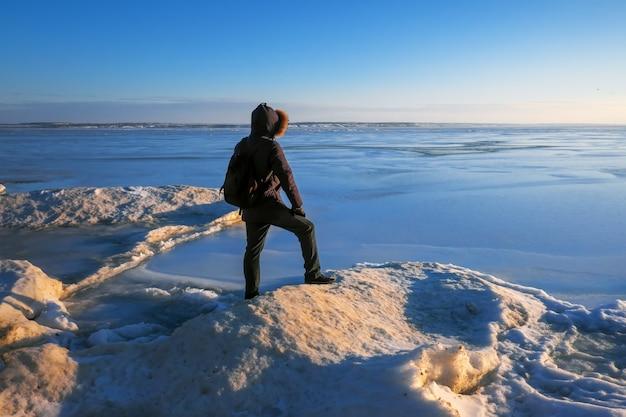 Homem no rio congelado durante o pôr do sol.