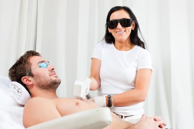Homem no salão de beleza cosmético recebendo depilação