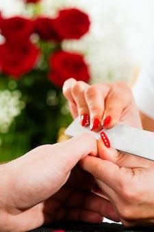 Homem no salão de beleza recebendo manicure
