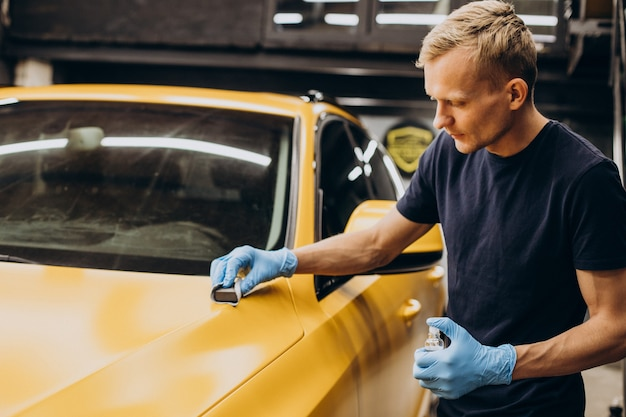 Homem no serviço de carro fazendo procedimento de cerâmica de carro