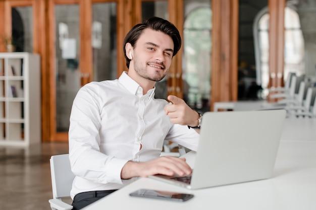 Homem no seu local de trabalho com telefone e laptop no escritório