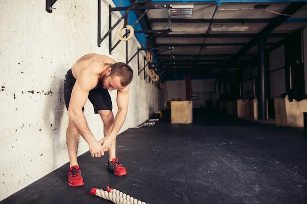 Homem no sportswear, dobrando-se com as mãos nos joelhos no ginásio