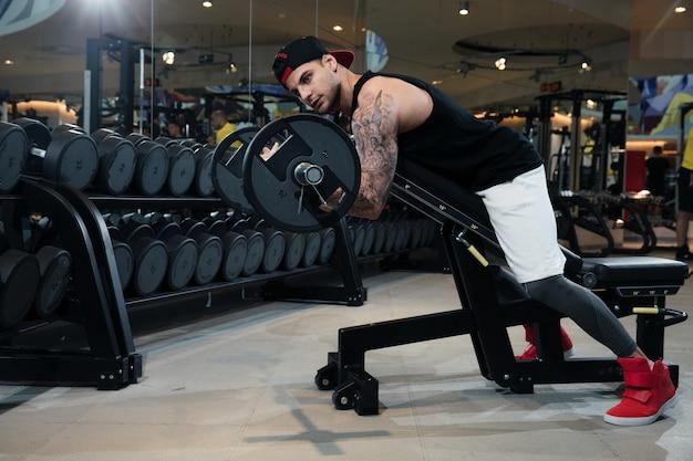 Homem no sportswear está treinando na academia