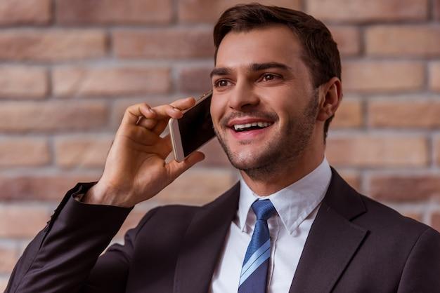 Homem no terno clássico que fala no telefone móvel.