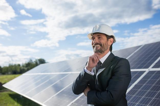 Homem no terno de negócio felizmente smailing, painéis solares em bastidores.