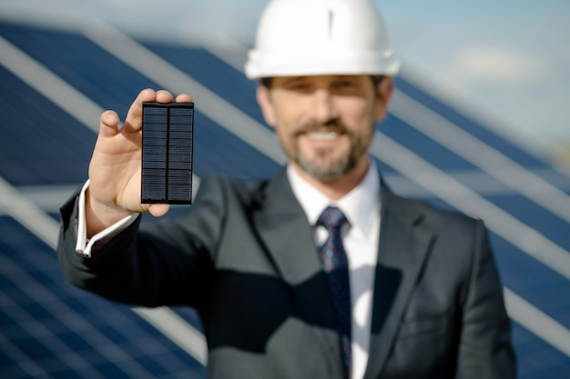Homem no terno de negócio que guarda o detalhe fotovoltaico de painel solar.